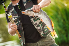 Homme tenant un poisson sur la rivière Photographie stock libre de droits