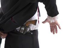 Homme tenant une arme à feu derrière le sien de retour Image libre de droits