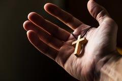 Homme tenant une croix en bois simple pendant le matin images libres de droits