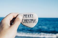 Homme tenant une pierre avec le Joyeux Noël des textes image libre de droits