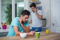Homme tendu à l'aide du téléphone à la table Photographie stock libre de droits