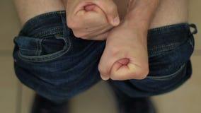 Homme tendu dans la toilette avec le problème serré de poings, de constipation ou de hemorrhoid clips vidéos