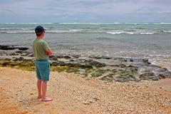 Homme tenu sur la plage Image stock