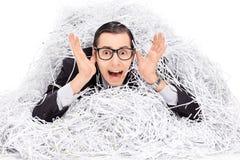 Homme terrifié couvert dans une pile de papier de défibreur Photographie stock