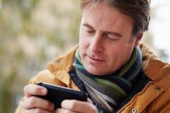 Homme Texting sur les vêtements s'usants de l'hiver de Smartphone Images stock
