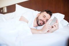 Homme textotant son amie dans le lit Images libres de droits