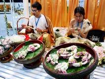 Homme thaïlandais et femme faisant des personnes de guirlande en démonstration dans traditionnel Image libre de droits
