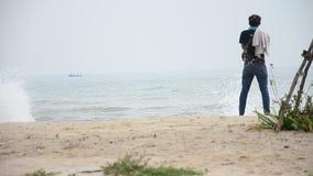 Homme thaïlandais stading à la plage de Chao Samran de chapeau de la mer dans Phetchaburi Thaïlande banque de vidéos