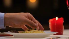 Homme tirant de longs cheveux hors du plat avec des spaghetti, états antihygiéniques de dégoût banque de vidéos
