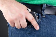 Homme tirant le canon hors de la poche Image libre de droits