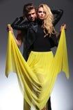 Homme tirant par la robe jaune de son amie Photos libres de droits