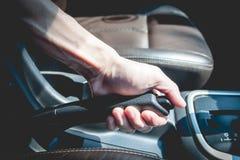 Homme tirant un handbreak dans une voiture Image libre de droits