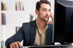 Homme étonné regardant un moniteur d'ordinateur Photos libres de droits