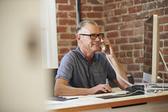 Homme travaillant à l'ordinateur dans le bureau contemporain Photos stock