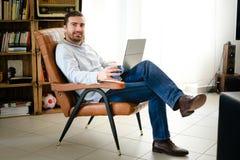 Homme travaillant à la maison utilisant son ordinateur portable Photos libres de droits