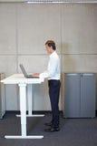 Homme travaillant à la table électriquement commandée de réglage de la hauteur photographie stock
