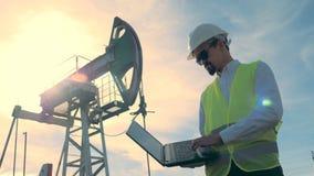 Homme travaillant à un gisement de pétrole avec un ordinateur portable, fin  banque de vidéos