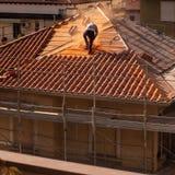 Homme travaillant à un toit et à un échafaudage pour la rénovation du vieux bâtiment image libre de droits