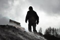 Homme travaillant à une pile de charbon de bois Images stock