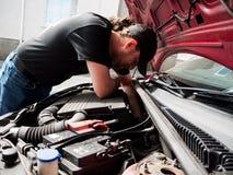 Homme travaillant à une voiture images stock