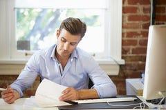 Homme travaillant au bureau dans le bureau contemporain photographie stock libre de droits