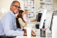 Homme travaillant au bureau dans le bureau créatif occupé photographie stock libre de droits