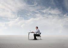 Homme travaillant au milieu d'un désert Image stock