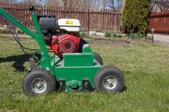 Homme travaillant avec l'aérateur de pelouse Image stock