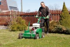 Homme travaillant avec l'aérateur de pelouse Images stock