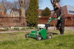 Homme travaillant avec l'aérateur de pelouse Photo stock