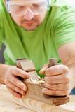 Homme travaillant avec l'avion du charpentier Photos stock