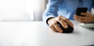 homme travaillant avec l'ordinateur de bureau et à l'aide du téléphone intelligent dans le bureau photo stock
