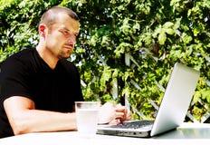 Homme travaillant avec l'ordinateur portatif à l'extérieur Image libre de droits