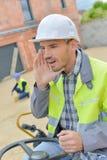 Homme travaillant avec le chargeur de dérapage image stock