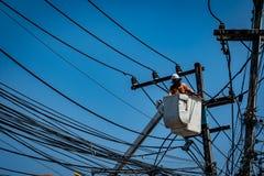 Homme travaillant avec le poteau de ligne électrique Image stock