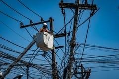 Homme travaillant avec le poteau de ligne électrique Photo libre de droits