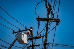 Homme travaillant avec le poteau de ligne électrique Photos libres de droits