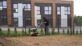 Homme travaillant dans le jardin avec la machine de talle Cultivé, cultivateur Mouvement de cardan banque de vidéos
