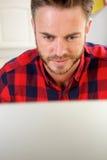 Homme travaillant derrière l'écran d'ordinateur Photographie stock libre de droits