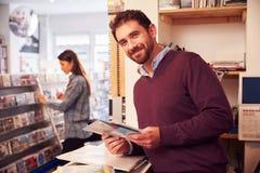 Homme travaillant derrière le compteur à une boutique record, portrait photo stock