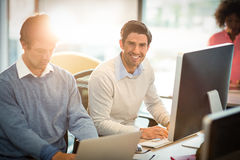 Homme travaillant sur l'ordinateur avec le collègue images libres de droits