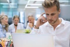 Homme travaillant sur l'ordinateur dans le bureau Photographie stock libre de droits