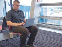Homme travaillant sur l'ordinateur nomade à l'aéroport photos stock