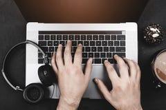 Homme travaillant sur l'ordinateur portatif Mains dactylographiant sur le clavier et les écouteurs au-dessus du fond noir de bure image stock