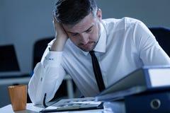 Homme travaillant tard au bureau Photographie stock libre de droits
