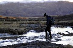Homme traversant un fleuve. images stock