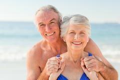 Homme étreignant son épouse à la plage Photos libres de droits