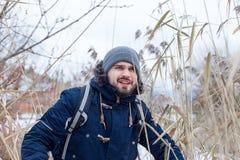 Homme trimardant dans les bois passant par un bosquet image stock