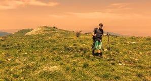 Homme trimardant en montagnes vertes Photographie stock libre de droits