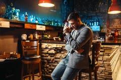 Homme triste avec le verre au compteur en bois de barre images stock